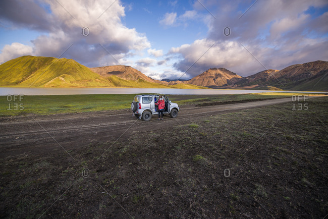 Woman traveler enjoying scenic view beside vehicle, Landmannalaugar, Highlands, Iceland