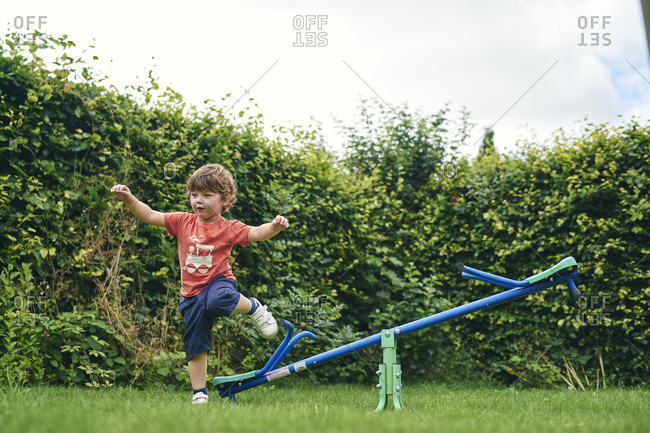 Boy hopping off toy seesaw in garden