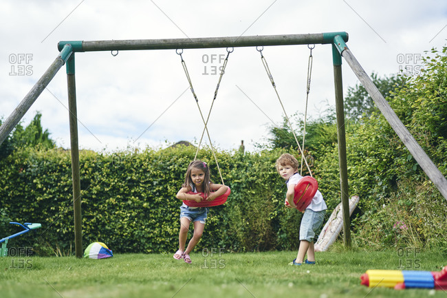 Girl and boy twisting around on swings in garden
