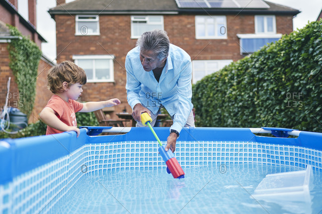 Grandfather helping boy fill up water gun from pool water