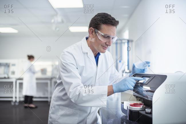 Scientist operating agar dish coating machine in laboratory