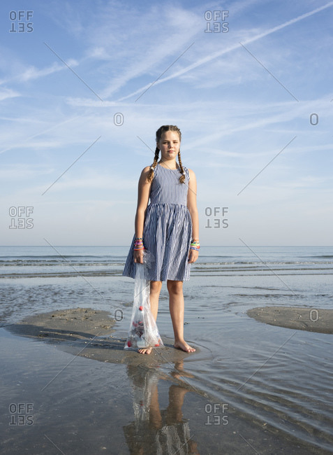 Girl collects plastic waste from beach, Hoek van Holland, Netherlands