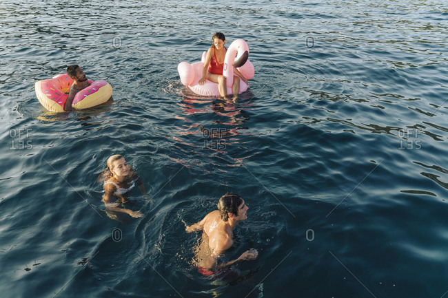 Friends swimming and relaxing on floats on sea, Italy