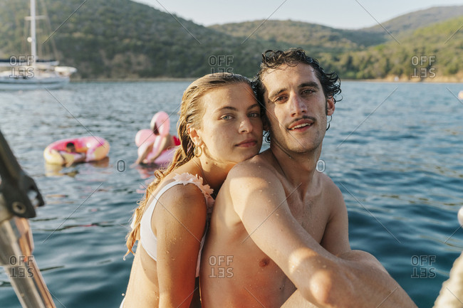 Couple taking selfie, friends relaxing on floats in background, Italy