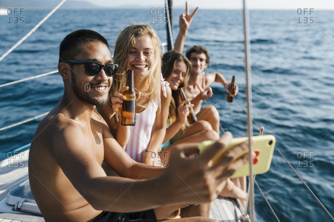 Friends taking selfie on sailboat, Italy