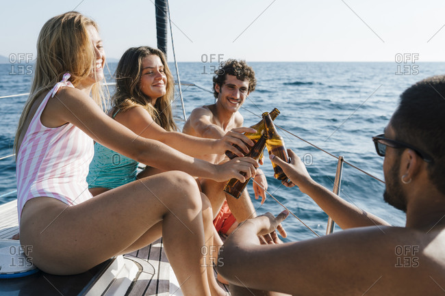 Friends toasting with beer on sailboat, Italy
