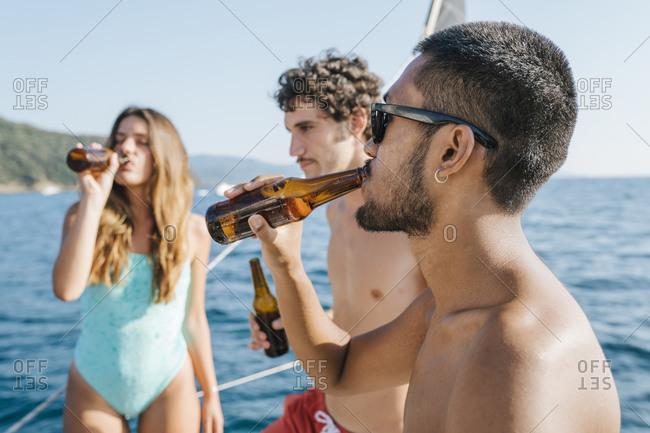 Friends enjoying beer on sailboat, Italy