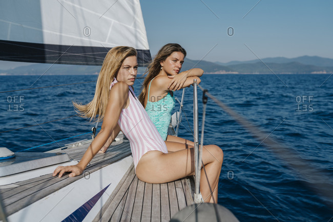 Friends relaxing on deck edge of sailboat, Italy