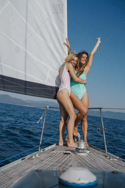 Women laughing and excited on bow of sailboat, Italy