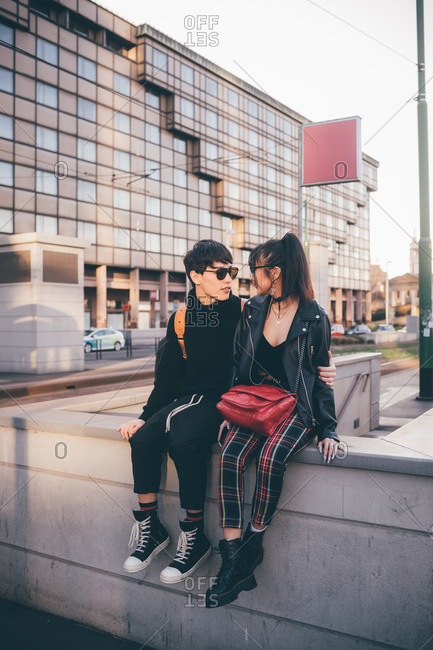 Trendy couple sitting on concrete structure, Milan, Italy