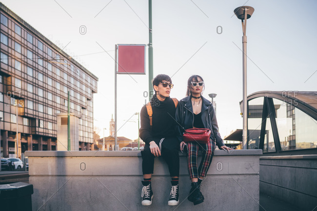 Trendy couple waiting on concrete structure, Milan, Italy