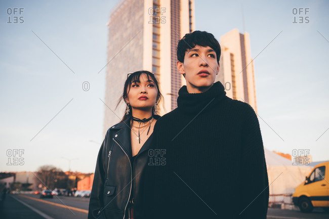 Young couple, high-rise building in background, Milan, Italy