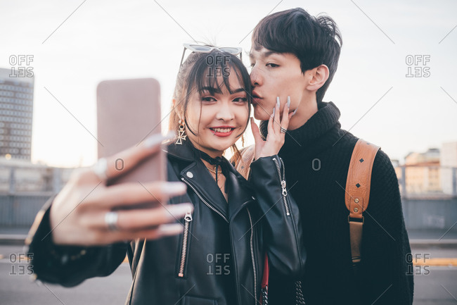 Young couple taking selfie on street, Milan, Italy