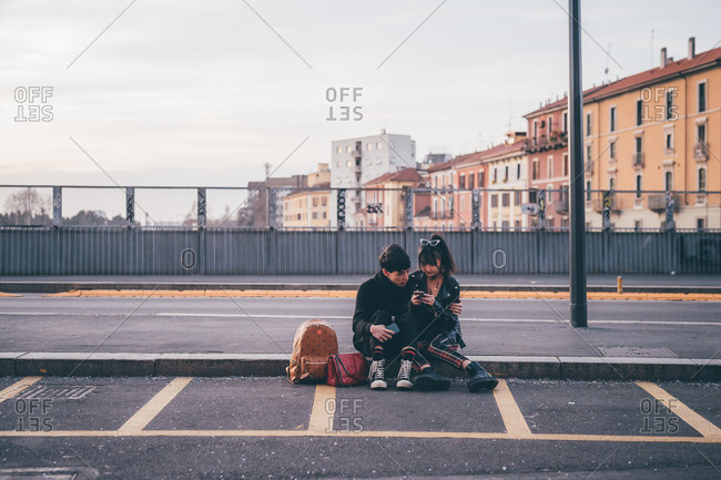Young couple texting on kerb, Milan, Italy