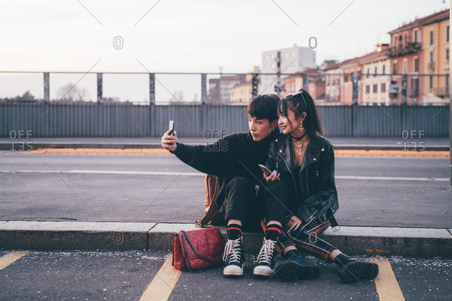 Young couple taking selfie on kerb, Milan, Italy