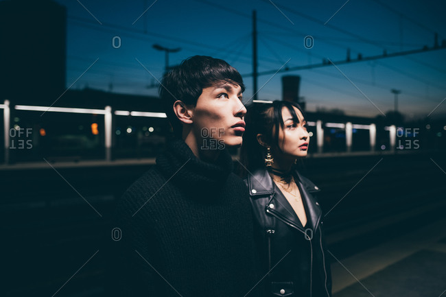 Couple with blank expression in train station, Milan, Italy