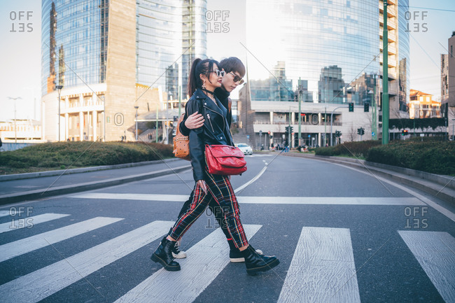 Young couple using pedestrian crossing, Milan, Italy