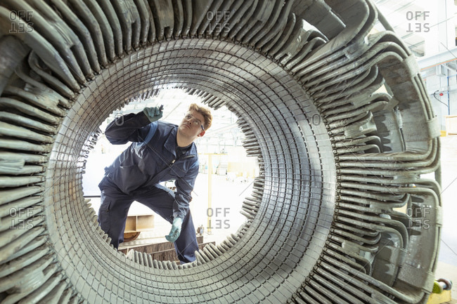 Electrical engineer inspecting winding on generator stator in electrical engineering factory