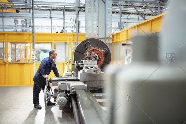 Wide angle view of engineer operating lathe in electrical engineering factory