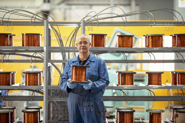 Portrait of electrical engineer with reel of copper wire in electrical engineering factory