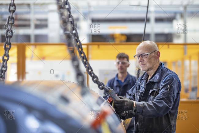 Engineers craning generator in electrical engineering factory
