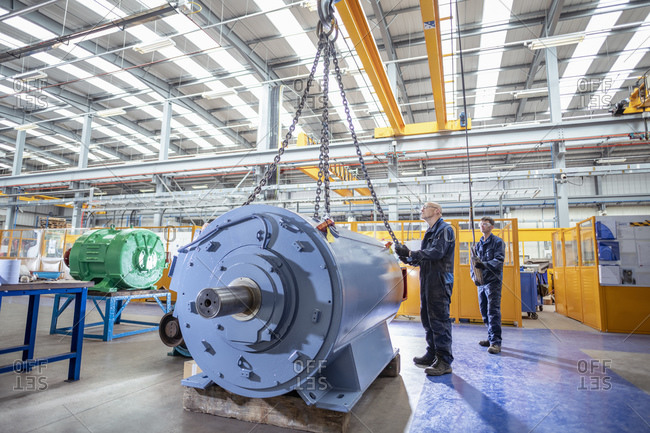 Engineers craning generator on to test bed in electrical engineering factory