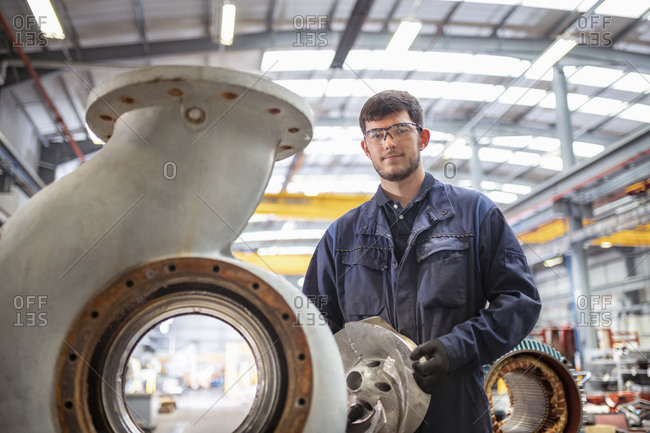 Portrait of apprentice engineer with snail shaped pump housing in electrical engineering factory