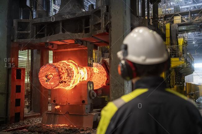 Red hot steel ingot in steel press in steelworks