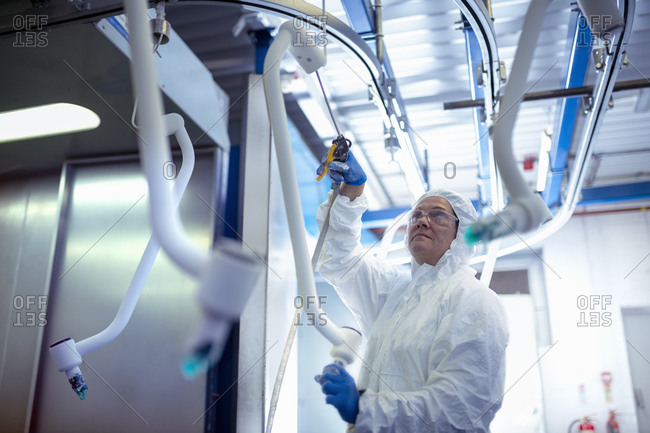 Worker in protective suit cleaning powder coated product in electronics assembly factory
