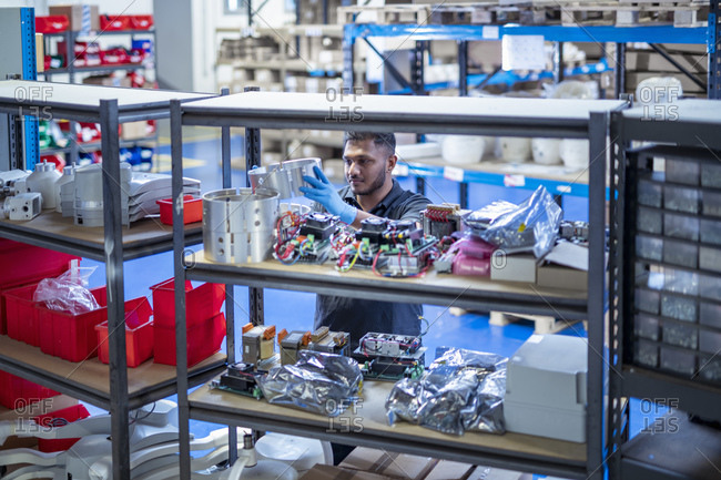 Worker picking products from stores in electronics assembly factory