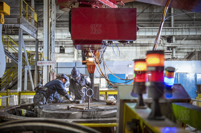 Workers making sand mold for pouring molten steel into steelworks