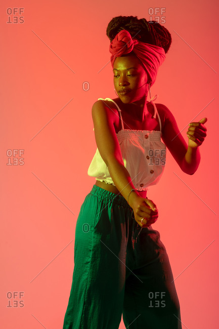 Woman with headscarf dancing against peach background