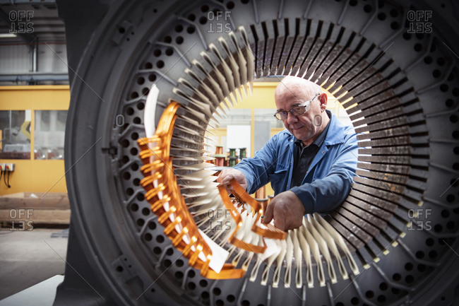 Electrical engineer installing copper windings into generator stator in electrical engineering factory