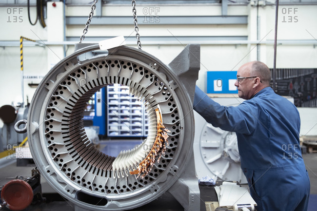 Electrical engineer craning generator stator in electrical engineering factory