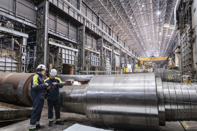 Workers inspecting large steel roller in forge of steelworks