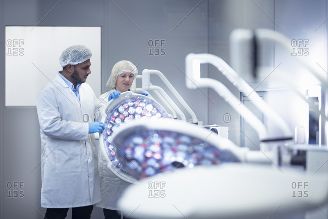 Workers in clean room assembling operating theatre lighting in electronics assembly factory