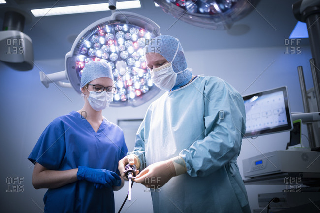 Nurse and surgeon in operating theatre in hospital setting