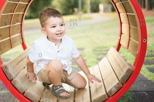 Toddler kneeling inside circular swing in park