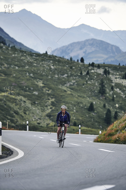 Male cyclist cycling on mountain road, Fluela Pass, Davos, Graubunden, Switzerland