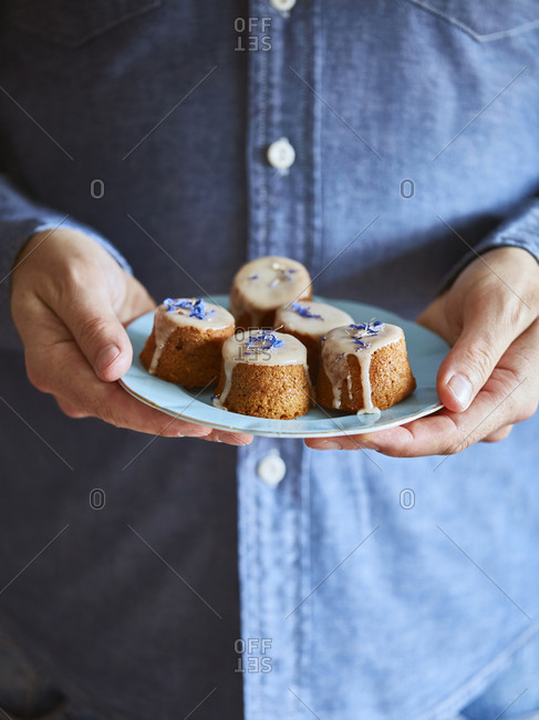 Man holding saucer of muffins