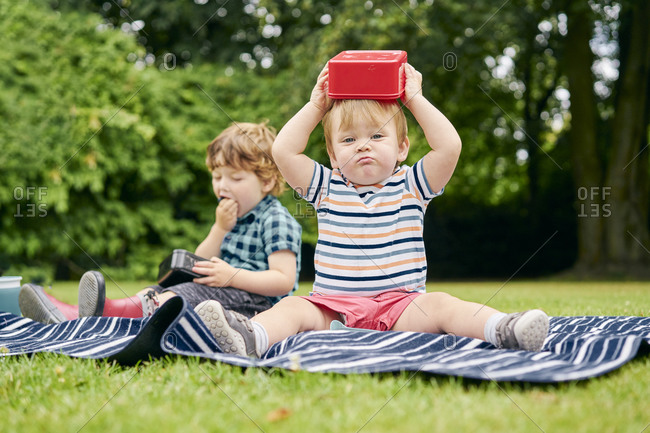 Brothers eating and playing on picnic blanket in park