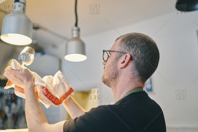 Waiter wiping wine glass in restaurant