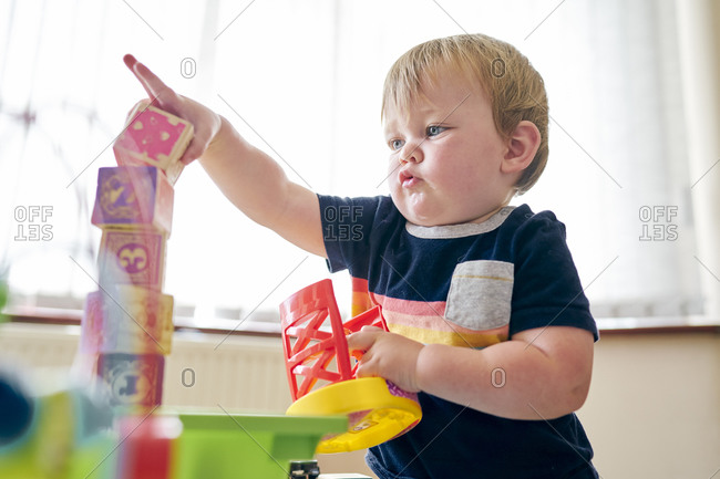 Toddler playing with building blocks in room