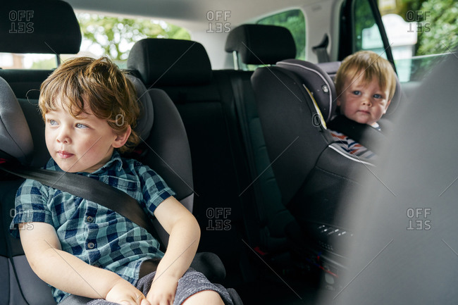 Brothers strapped onto child car seats in the back seat of a family car.