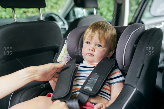 Toddler being strapped into a child car seat in the back of a family car.