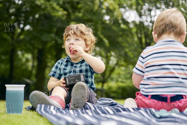 Toddler eating in park - Offset