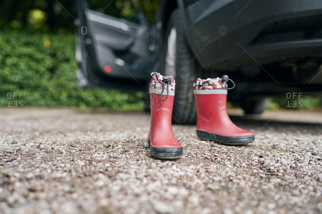 Pair of child's red ankle boots on gravel road