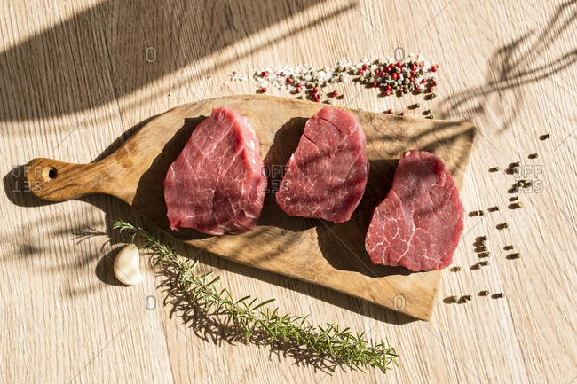 Thick slices of raw meat, rosemary, peppercorn