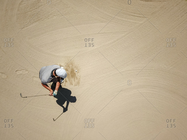 Man playing golf on bunker
