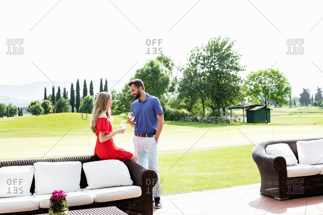 Couple with wine glasses talking beside sofa on golf course